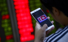 An investor looks at his smartphone showing results from the US presidential election, at a securities company in Beijing on November 9, 2016