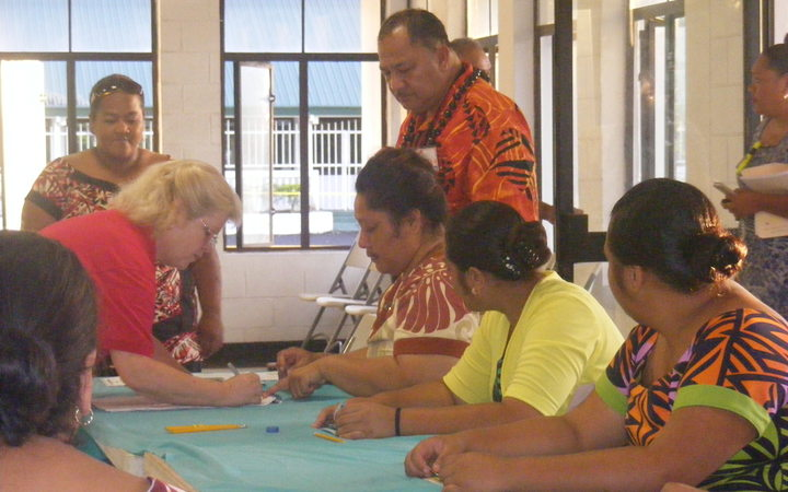 A voter in American Samoa signs on the voter rolling at the Ili'ili polling station.