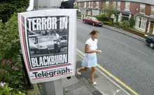 A pedestrian walks past a newspaper front page announcing the arrest of suspects on terrorism charges on Old Preston Road in Blackburn, Lancashire.