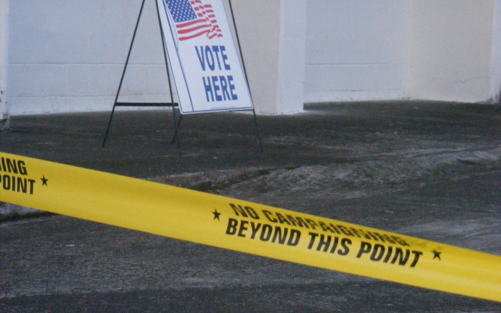 "A ""Vote Here"" sign, with yellow tape ""no campaign beyond this point"" is a common scene for voters entering one of the 44-polling stations in American Samoa."