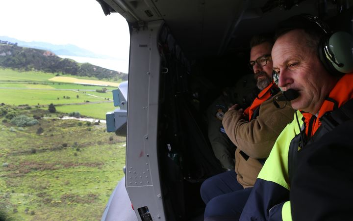 New Zealand Prime Minister John Key (R) inspects earthquake damage from a helicopter near Kaikoura.