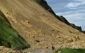 Emergency services officers inspect the damage caused to Rotherham Road near Waiau town.