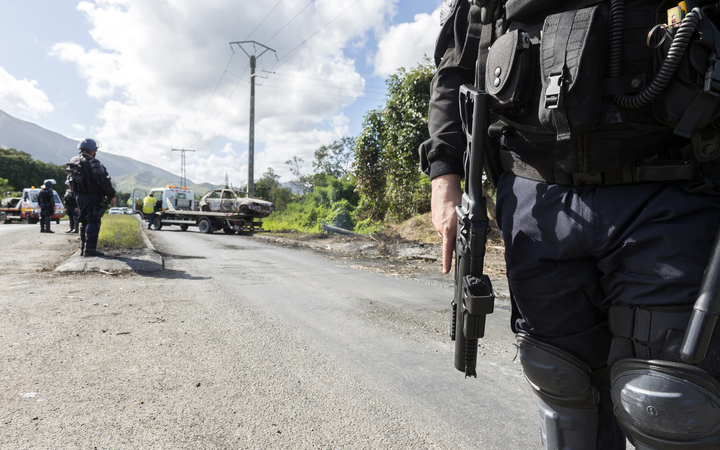 French police officers stand guard on a road in Mont-Dore, a suburb of Noumea, in New Caledonia, on May 28, 2014, while a tow lifts the wreckage of a burned car. Angry residents from the Saint Louis tribal group burned cars creating roadblocks on May 24, 2014