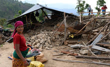 A villager stands near a damaged house at Arupokhari in Gorkha.