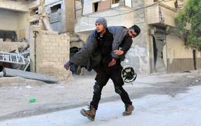A Syrian civil defence volunteer, known as the White Helmets, carried an injured man following air strike on Aleppo's rebel-held neighbourhood of Bab al-Nayrab.