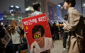 A protester in Seoul holds a sign calling for the resignation of President Park Geun-hye.