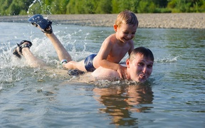 A father and his young son swim in a river (file)