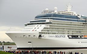 "Onlookers watch luxury cruise liner ""Celebrity Solstice"" being towed past a lock on the Ems river in Gandersum, northern Germany, on September 29, 2008. The ship, Germany's biggest of its kind, built at the Meyer Werft shipyards in Papenburg, is due to reach the North Sea over the Ems river."