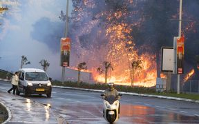 Israelis drive past a fire in the northern Israeli port city of Haifa.