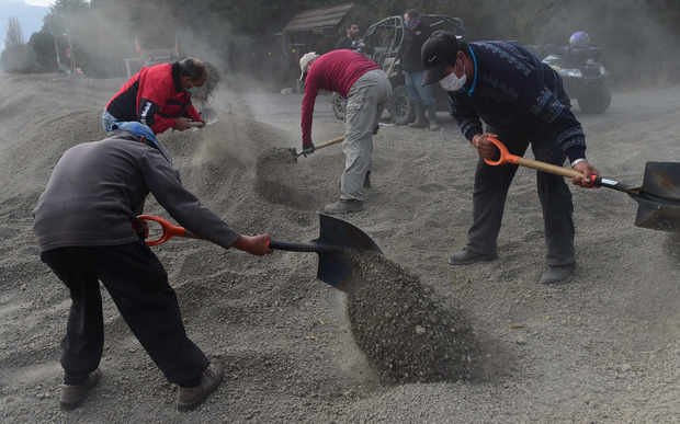 Local residents remove ashes from a street in La Ensenada after last week's eruption.