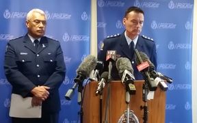 Inspector Willi Fanene and Inspector Mark Fergus talking to the media.