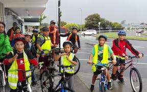 A group of kids in Hi-Viz vests with bikes