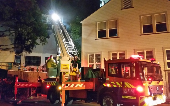 Fire fighters check the ceiling cavities for spread of the fire.
