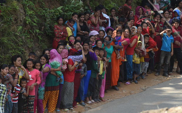 Nepalese people queue for relief aid from an Indian Air Force (IAF) helicopter team in northern-central Gorkha.