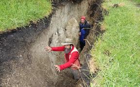 Two geologists standing in a trench