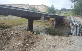 A damaged bridge and temporary replacement bridge on the road between Waiau and Mt Lyford.