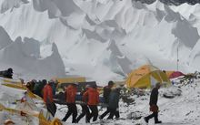 Rescue team personnel carry an injured person towards a waiting rescue helicopter at Everest Base Camp.