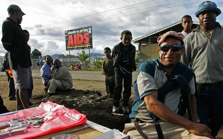 Residents sell their goods near a anti-Aids billboard in Mount Hagen, 18 August 2007.