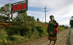 A woman walks past a HIV/AIDS billboard in PNG
