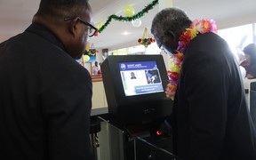 Solomon Islands Prime Minister Manasseh Sogavare (R) tries out the newly launched E-passport and Border Control and Management system. Looking on (L) is the Deputy Prime Minister Manasseh Maelanga.