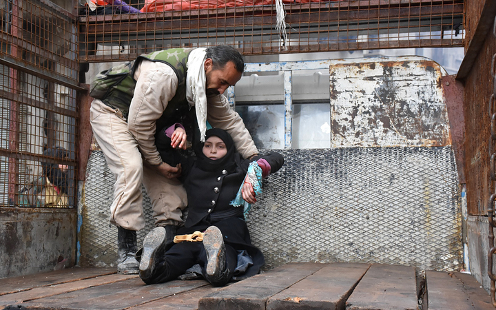A wounded Syrian woman is helped onto the back of a truck as she flees during the ongoing government forces military operation in Aleppo on 14 December, 2016.