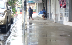 Fijians shelter from heavy rain in Nadi.