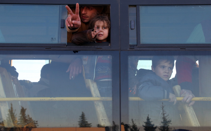 Syrians, who were evacuated from rebel-held neighbourhoods in the embattled city of Aleppo, arrive in the opposition-controlled Khan al-Aassal region, west of the city, on December 15, 2016, the first stop on their trip.