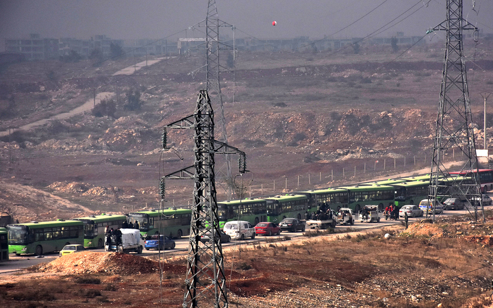 Buses are seen during an evacuation operation of Syrian rebel fighters and civilians from a opposition-held area of Aleppo towards rebel-held territory in the west of Aleppo's province on December 16