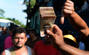 People hold up newly worthless 100-bolivar notes during a protest over lack of cash in the country.