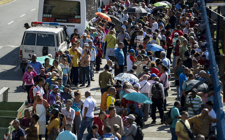 People queue outside Venezuela's Central Bank (BCV) in Caracas in an attempt to change 100-bolivar notes before they become worthless.
