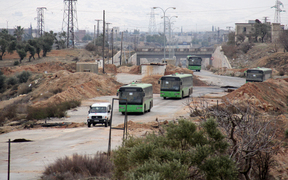 Buses sent to evacuate residents from Fuaa and Kafraya villages arrive at a rebel-held checkpoint on the outskirts of the two Syrian villages under rebel siege, on December 18, 2016.