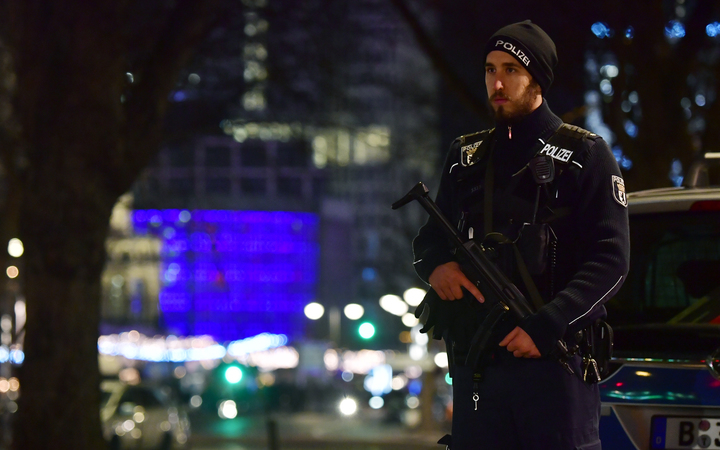 Police stand guard near the Berlin Christmas market after a truck ploughed into a crowd, killing nine.