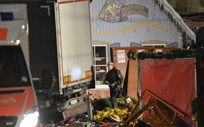 An officer inspects the truck after it crashed into a crowd near a Christmas market in Berlin.