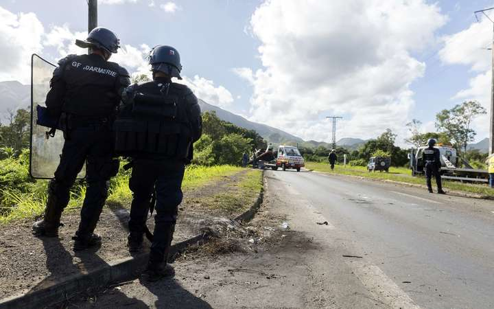 Police officers guard the road in Mont-Dore, to the south of New Caledonia's capital, Noumea. The road is frequently closed by armed protesters.