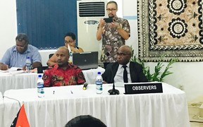 An Indonesian captures the Melanesian Spearhead Group proceedings, 20 December 2016 in Port Vila, on device. West Papuan representatives Benny Wenda and Octo Mote (MSG observers with the United Liberation Movement) in foreground.