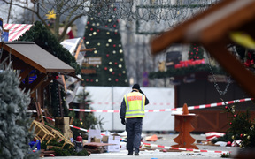 A policeman walks at the Christmas market near the Kaiser-Wilhelm-Gedaechtniskirche (Kaiser Wilhelm Memorial Church), the day after a terror attack, in central Berlin, on December 20.