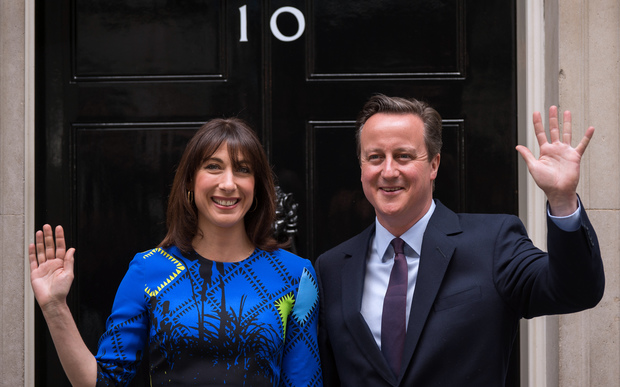 David Cameron and his wife Samantha pose for pictures as they arrive back at 10 Downing Street in London on 8 May.