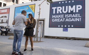 Two people stand in front of a 'Trump make Israel great again!' sign in Israel