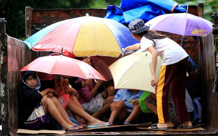 Young Phillipines residents sit in a truck after the local government implemented preemptive evacuations at Barangay Matnog, Daraga, Albay province, due to the approaching typhoon Nock-Ten