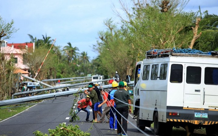 Workers check downed electric posts on the national road after typhoon Nock-Ten made landfall in Nabua, Camarines Sur.