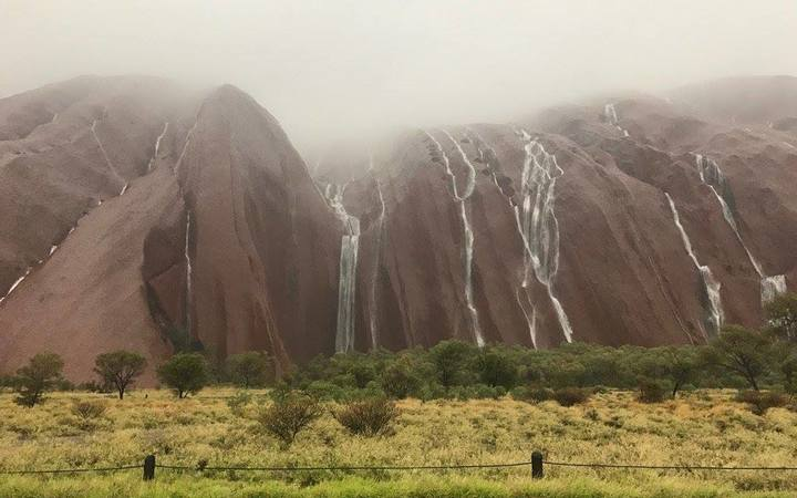 Waterfalls cascade down Uluru after flash flooding in central Australia