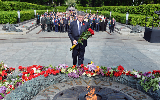 Ukrainian President Petro Poroshenko lays flowers at a memorial in Kiev on Saturday 9 May 2015.