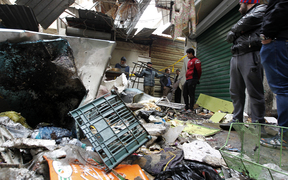 Iraqis look at the aftermath following a double blast in a busy market area in Baghdad's central al-Sinek neighbourhood on 31 December , 2016.