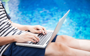 A man with a laptop checks his work emails by the pool (file).