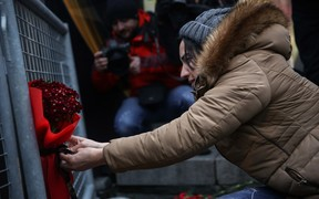 A woman leaves a bouquet of carnation at site to pay tribute to victims of Istanbul night club terror attack in Istanbul, Turkey on January 01, 2017.