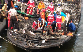Rescuers search the charred passenger boat which caught fire off the coast of Jakarta, killing 23 people.