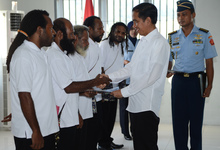 Indonesia's President Joko Widodo shakes hands with freed Papuan political prisoner Kimanus Wenda (2nd L) while four others Jefrai Murib (L) Apotnalogolik Lokobal (3rd L) Numbungga Telenggen (4th L) and Linus Hiluka (3rd R) during a ceremony at Abepura prison in Papua Province.