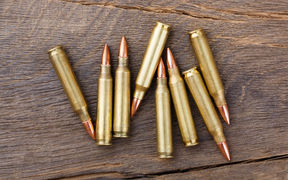 Fire arm or rifle bullet cartridges on a old wooden table.