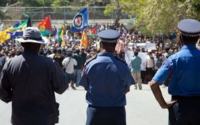 Papua New Guinea police officers watch on during a protest rally in 2013.