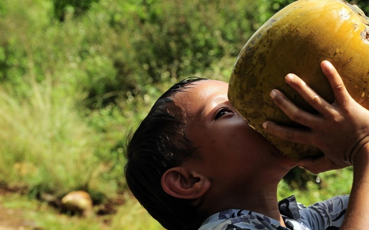 A Tongan child drinks from a coconut near the Tuanekivale medical site for Pacific Partnership 2011.